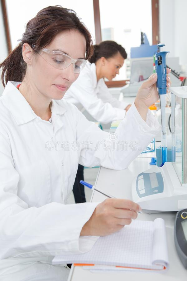 Female researcher recording experiment in notebook stock photos