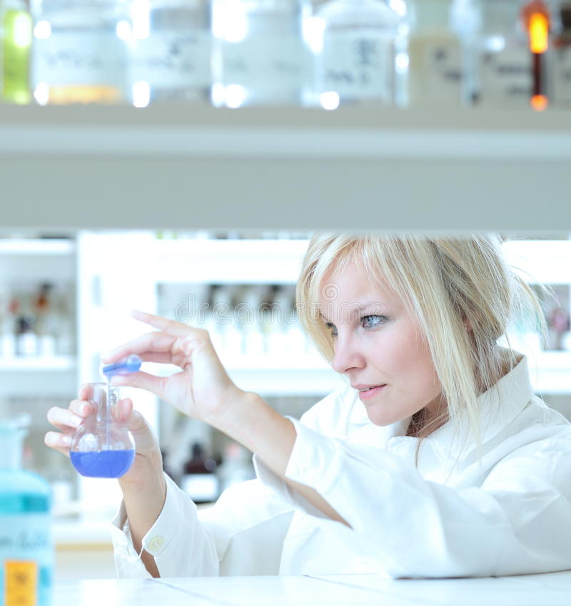Female researcher working in a lab. Closeup of a female researcher holding up a test tube and a retort and carrying out some experiments royalty free stock images