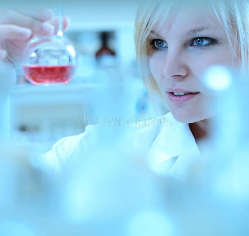 Female researcher working in a lab. Closeup of a female researcher carrying out an experiment in a lab royalty free stock photography