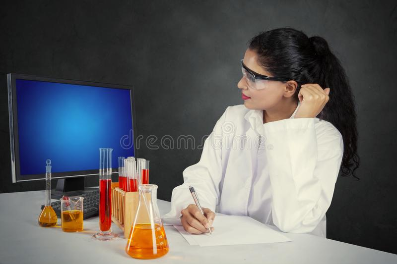 Female researcher writing on a paper stock photography