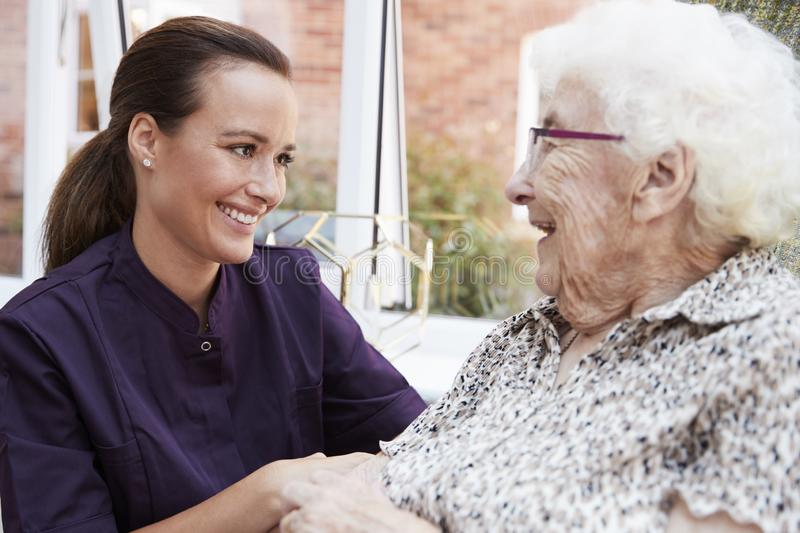Female Resident Sitting In Chair And Talking With Carer In Retirement Home stock photography