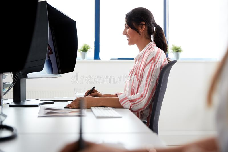 Female Retoucher Working At Computer Using Graphics Tablet In Post Production Company stock photos