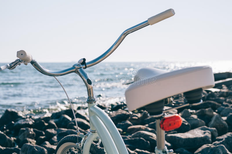 Female retro bicycle on the beach on a background of blue sea on. A sunny day, close-up royalty free stock photo