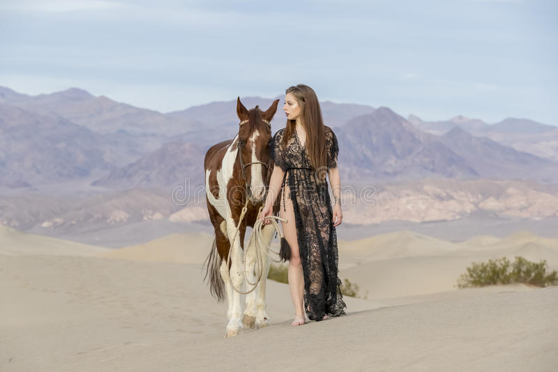 Female Rider And Her Horse. A female model riding her horse through the Mohave Desert royalty free stock photo