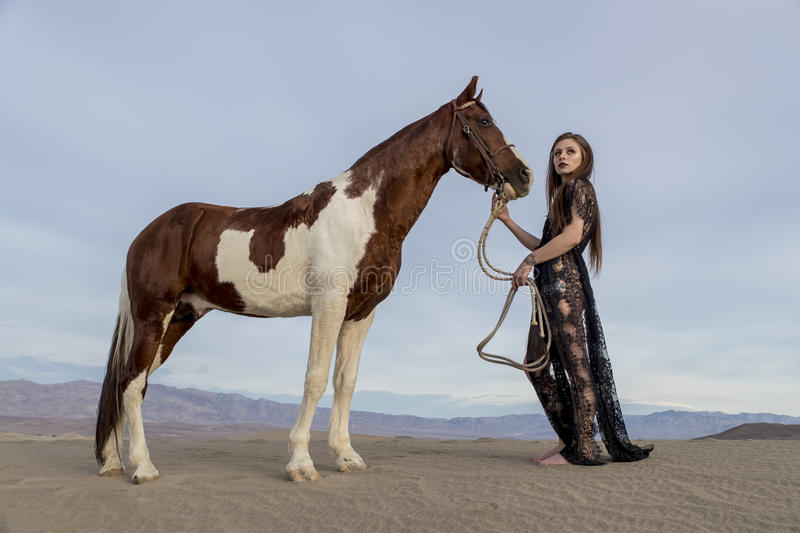 Female Rider And Her Horse. A female model riding her horse through the Mohave Desert royalty free stock images