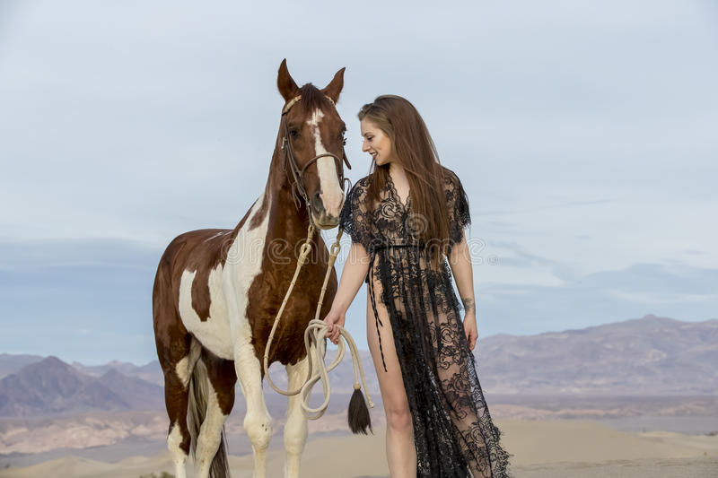 Female Rider And Her Horse. A female model riding her horse through the Mohave Desert stock photo