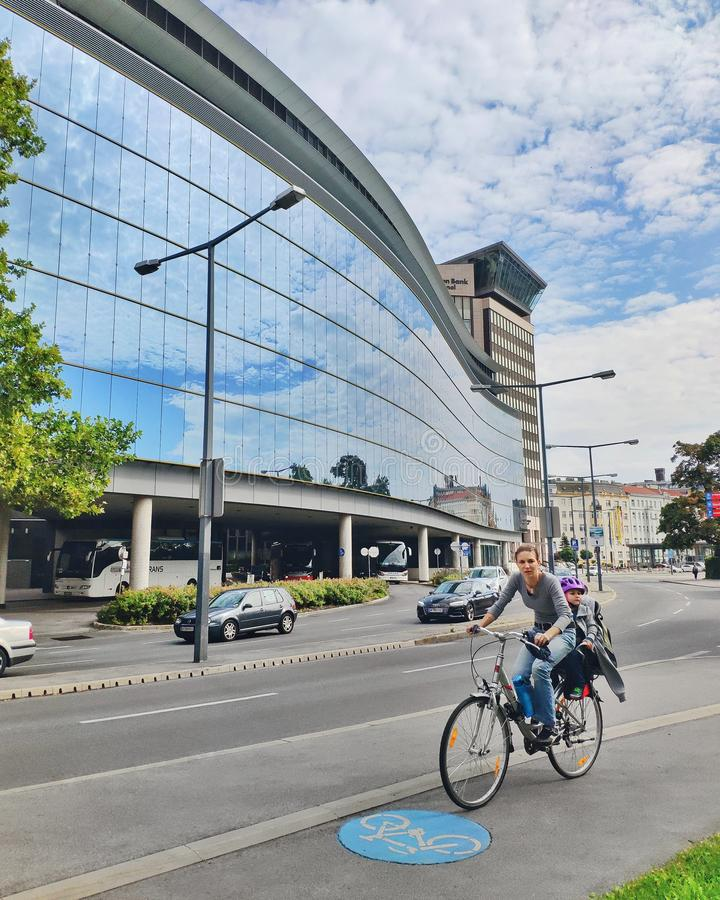 Female riding city bicycle with baby in bicycle chair on the bicycle path, against the background of modern glass building stock photo