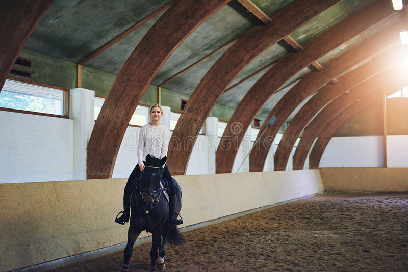 Female riding horse in indoor riding hall stock photography