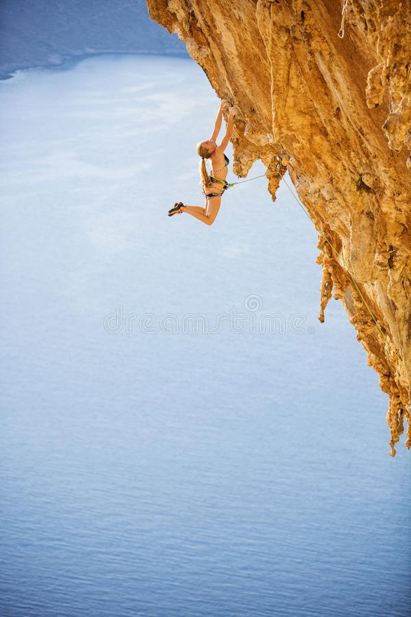 Female rock climber jumping on handholds on challenging route on cliff stock photo