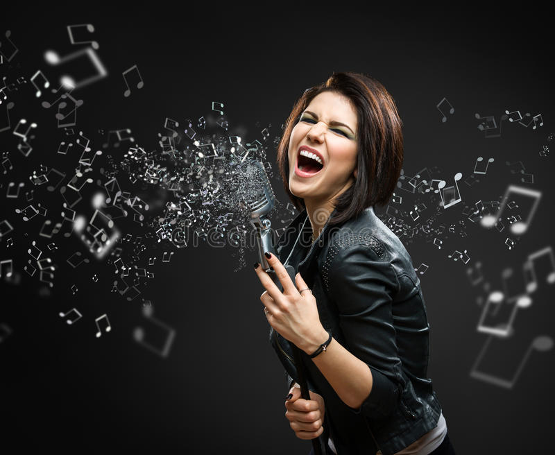 Female rock musician holding sounding mike with melody in the air. On grey background stock image