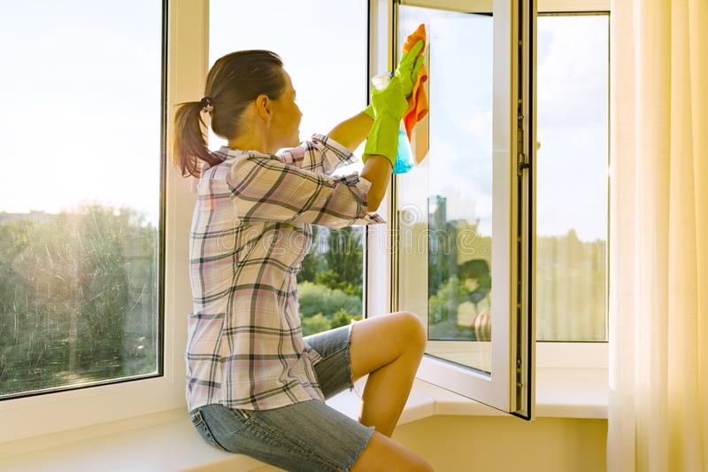 Female with rubber protective gloves, rag and sprayer detergent looks into a clean washed window stock photography