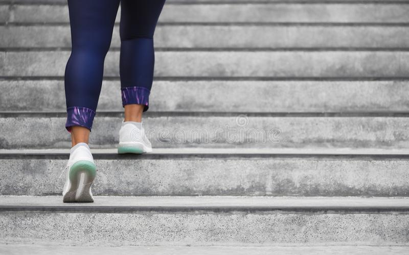 Female runner athlete doing a stairs climbing. Running woman doing run up steps on staircase in urban city. Doing cardio sport royalty free stock photography