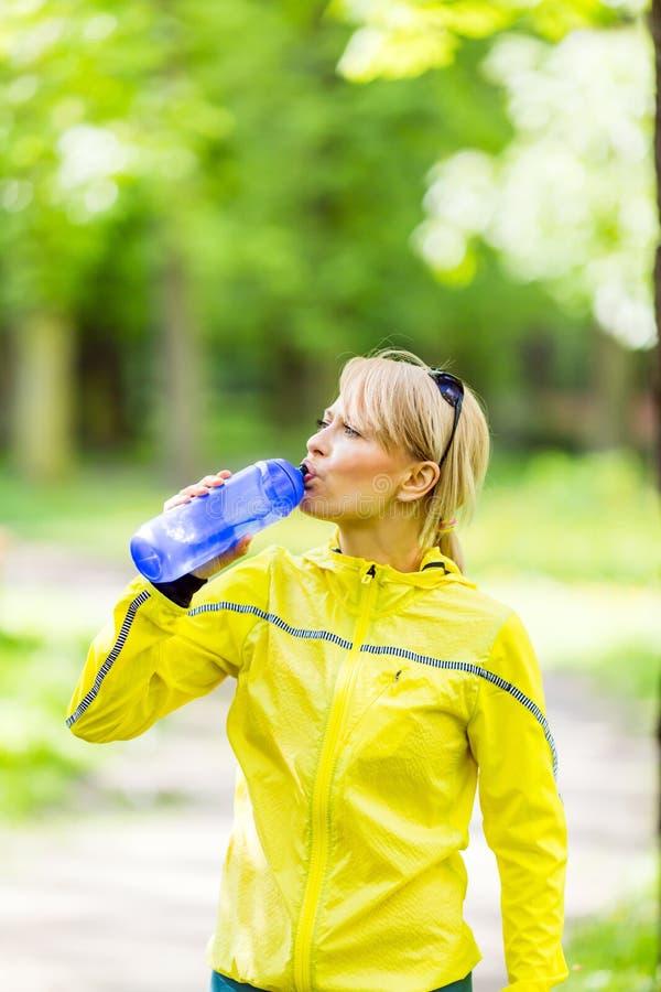 Female runner drinking water stock photos