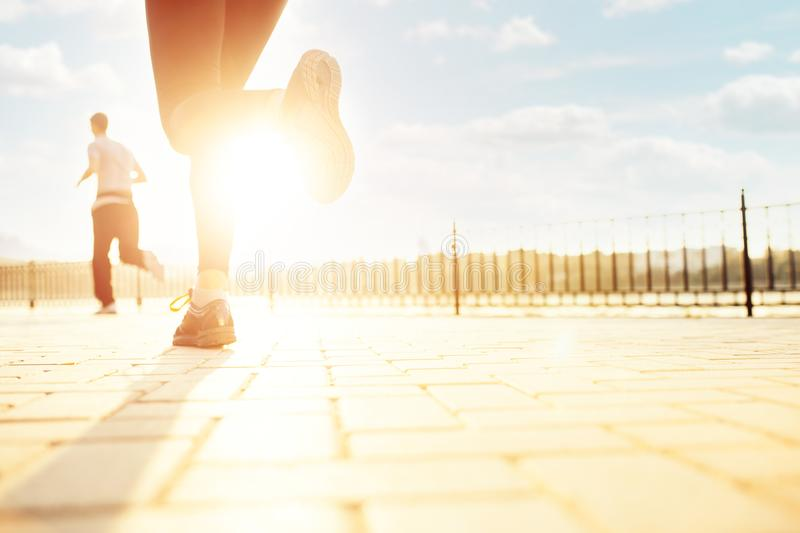 Female runner feet running at sunrise. People running in the city park, copy space on right. Woman legs running in the rays of sun. Female runner feet running at royalty free stock images