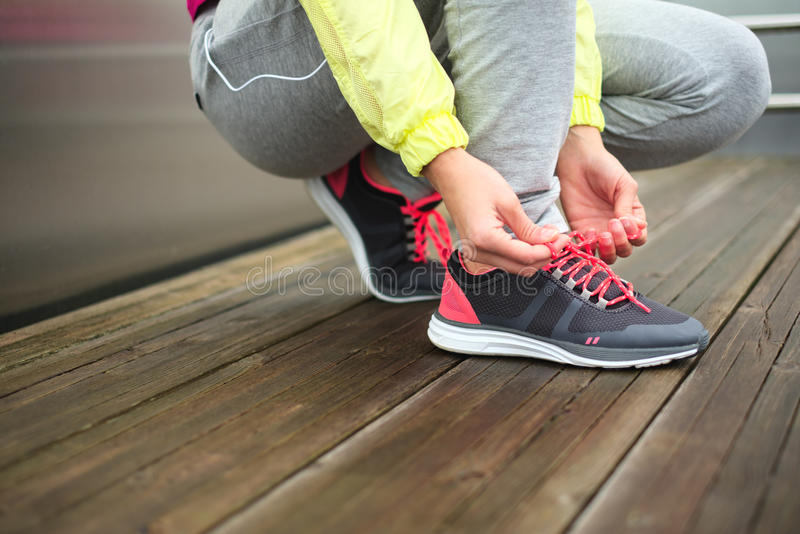 Female runner lacing running sport footwear. Female runner tying sport shoes laces before running urban challenge. Sporty unrecognizable woman lacing footwear royalty free stock images
