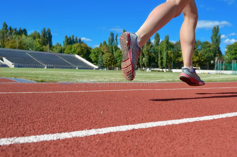 Female runner legs in shoes on stadium track, woman athlete running and working out outdoors, sport and fitness stock photos