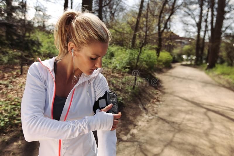 Female runner monitor her progress on smartphone. Beautiful young woman training outdoors while using a smartphone to monitor her progress. Caucasian female stock image