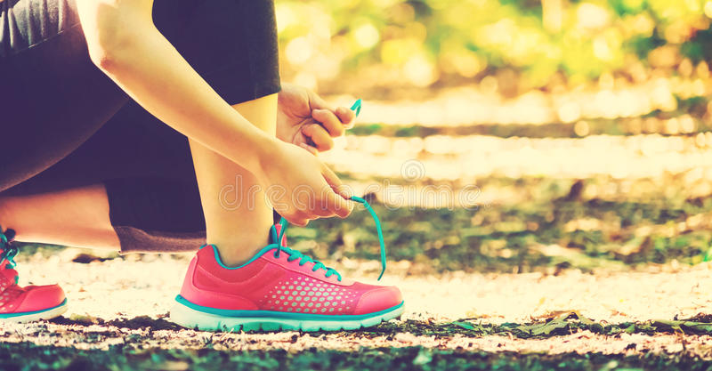 Female runner preparing to jog. Female runner preparing to go for a jog outdoors royalty free stock photo