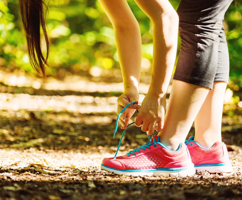 Female runner preparing to jog. Female runner preparing to go for a jog outdoors royalty free stock photos