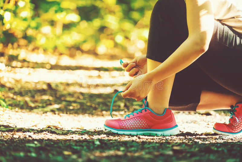 Female runner preparing to jog. Female runner preparing to go for a jog outdoors stock photography