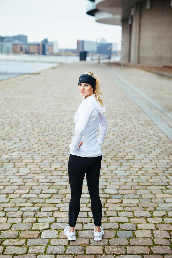 Female runner ready for a city run. Outdoor shot of young woman standing on sidewalk looking over shoulder. Fitness female model ready for a city run royalty free stock image