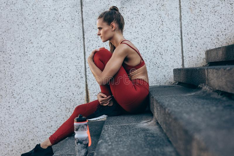 Female runner resting after workout stock image