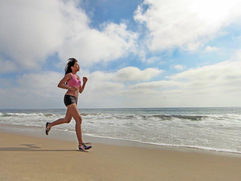 Female Runner Running at the Beach Jogging stock images