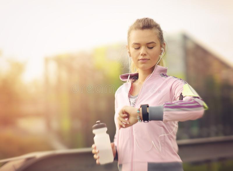 Female runner running at sunset in city park - Healthy fitness woman jogging outdoors - Athlete listening to music during workout royalty free stock photography