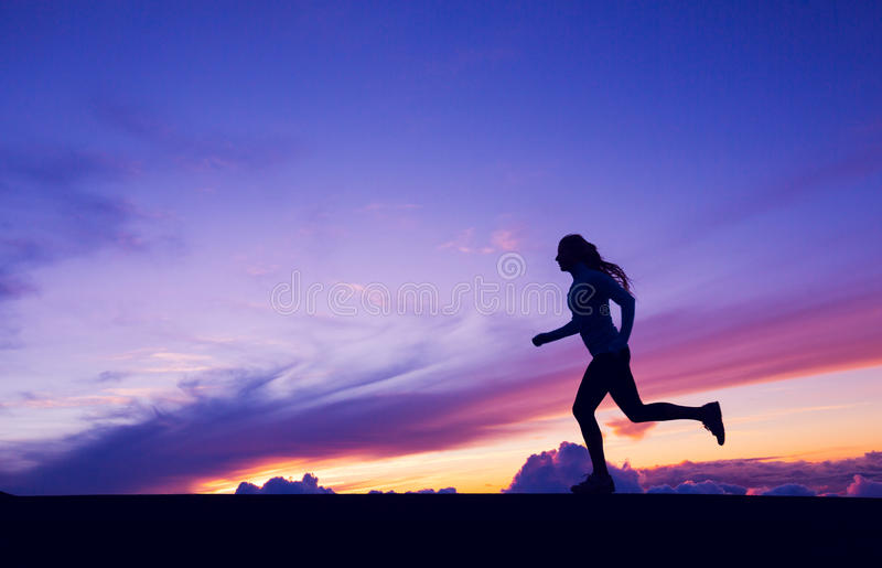 Female Runner Silhouette, Woman Running into sunset. Colorful sunset sky stock photography