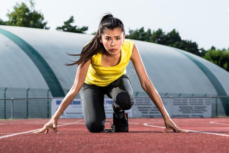 Female Runner before start signal on starting block of sprint tr stock photos