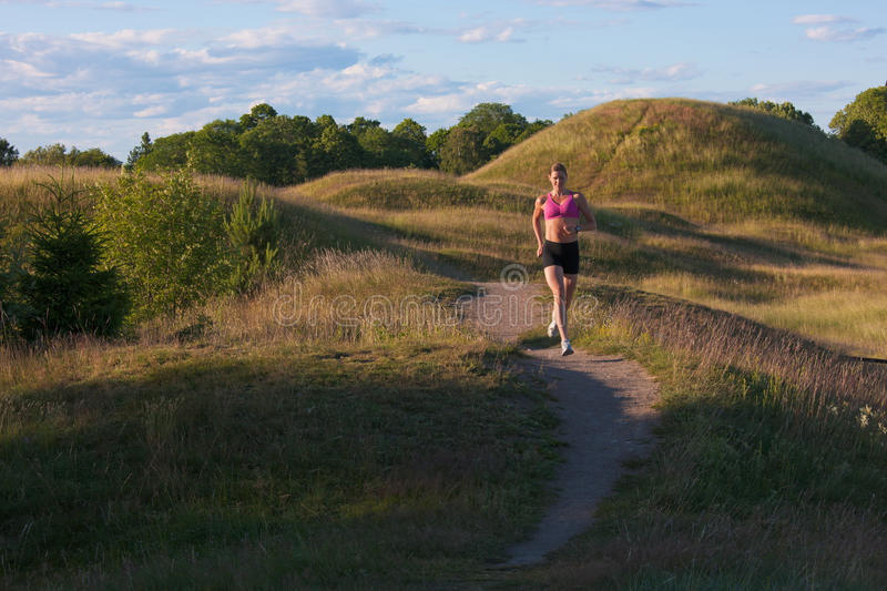 Female runner in a stunning summer landscape royalty free stock photography