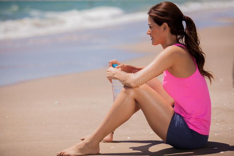 Female runner taking a break. Happy Latin woman taking a break to drink water after jogging at the beach royalty free stock photography
