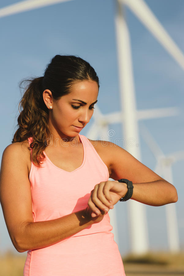 Female runner timing workout. Female motivated athlete using sport watch for timing running workout. Sporty woman training outdoor royalty free stock image