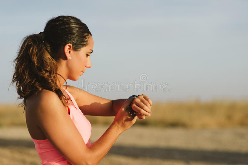 Female runner timing workout. Female motivated athlete using sport watch for timing running workout. Sporty woman training outdoor stock photography