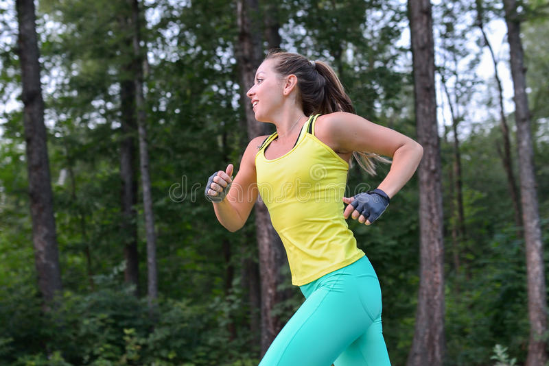 Female runner training outdoor in profile. Healthy lifestyle image of young woman jogging outside. royalty free stock images