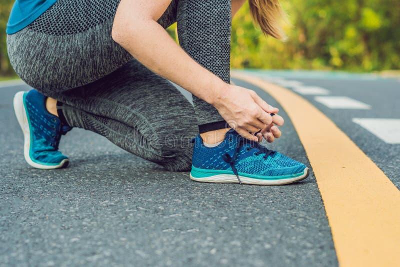 Female runner tying her shoes preparing for jogging outside .Young girld runner getting ready for training. Sport stock photo