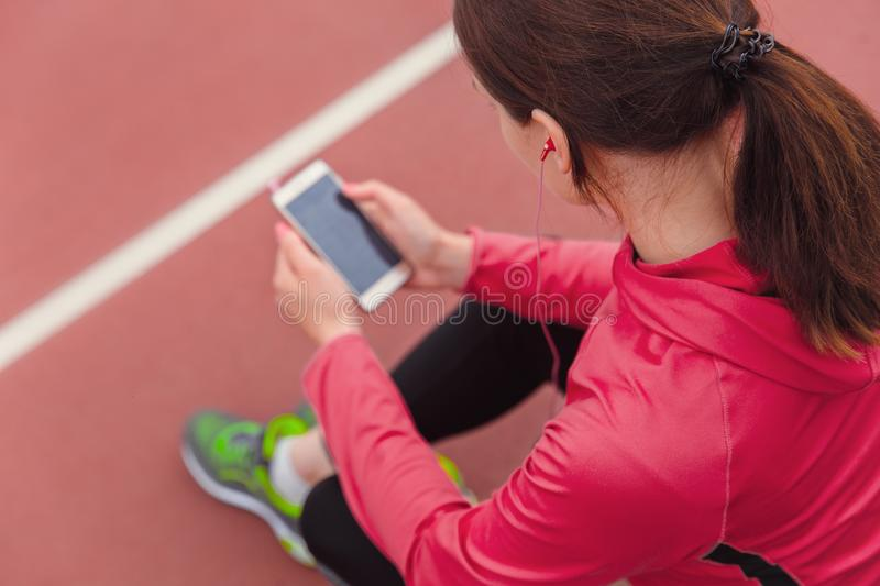 Female runner using cell phone and listening to music while resting after jogging stock images