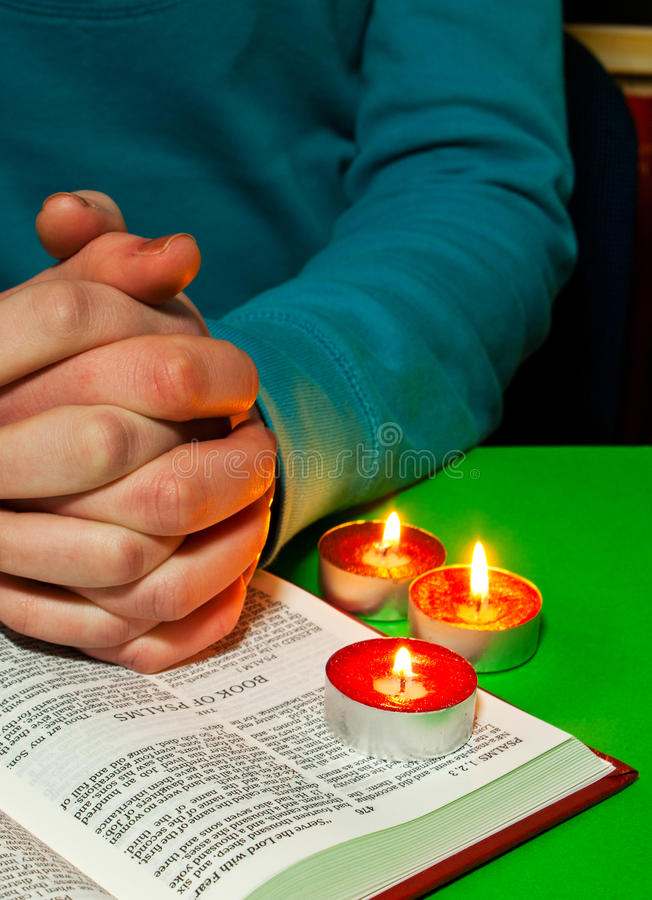 Female's arms over the Book of Psalms. With burning candles. Text of Bible is the King James version which is public domain royalty free stock photo