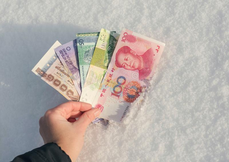 A female`s hand is holding money of south-east Asia above the snow. Currency of Hong Kong, Indonesia, Malaysia, China. Thailand stock photo