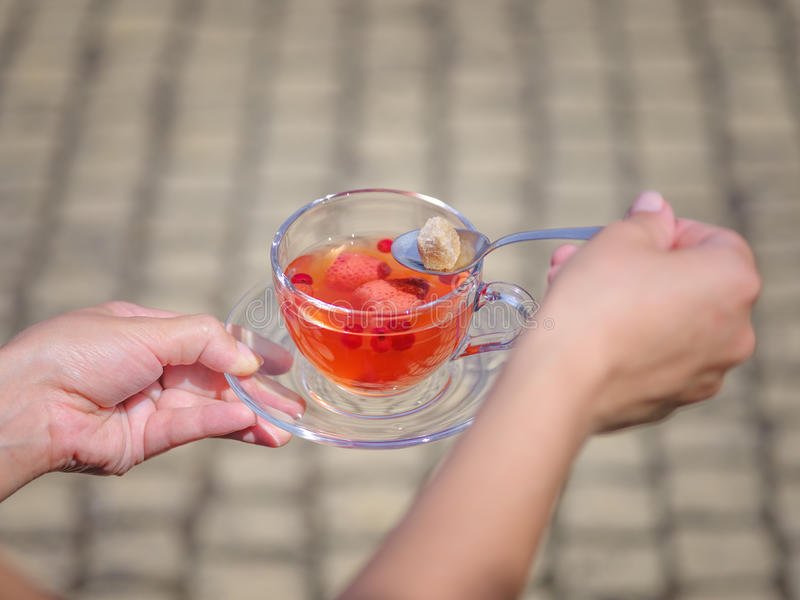 A female`s hands with a cup of berries liquid on a stone blurred background. Delicious and natural strawberry tea. royalty free stock photography
