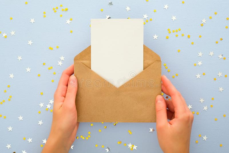 Female`s hands holding kraft paper envelope letter with blank white card mockup over pastel blue background with golden confetti stock image