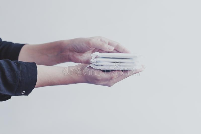 Female`s hygiene products. Woman`s hand holding a stack of sanitary napkins against white background. Period days concept showin. Female`s hygiene products royalty free stock photography