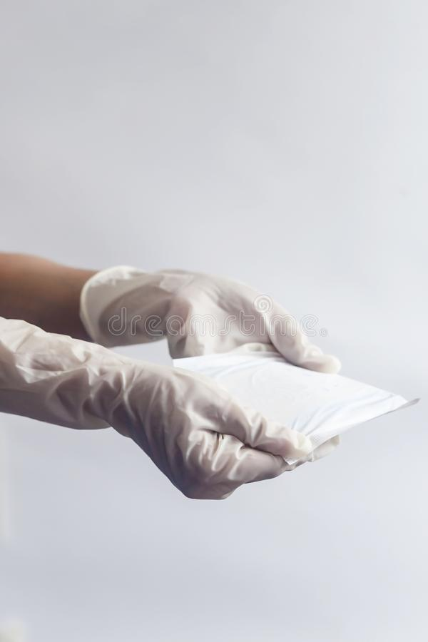 Female`s hygiene products. Woman`s hands in medical gloves holding sanitary napkins against white background. Period days concep. Female`s hygiene products stock photography