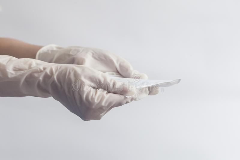 Female`s hygiene products. Woman`s hands in medical gloves holding sanitary napkins against white background. Period days concep. Female`s hygiene products stock photos