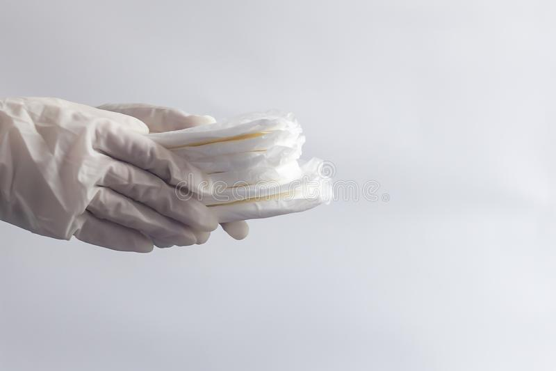 Female`s hygiene products. Woman`s hands in medical gloves holding a stack of sanitary napkins against white background. Period. Female`s hygiene products. Woman stock photo