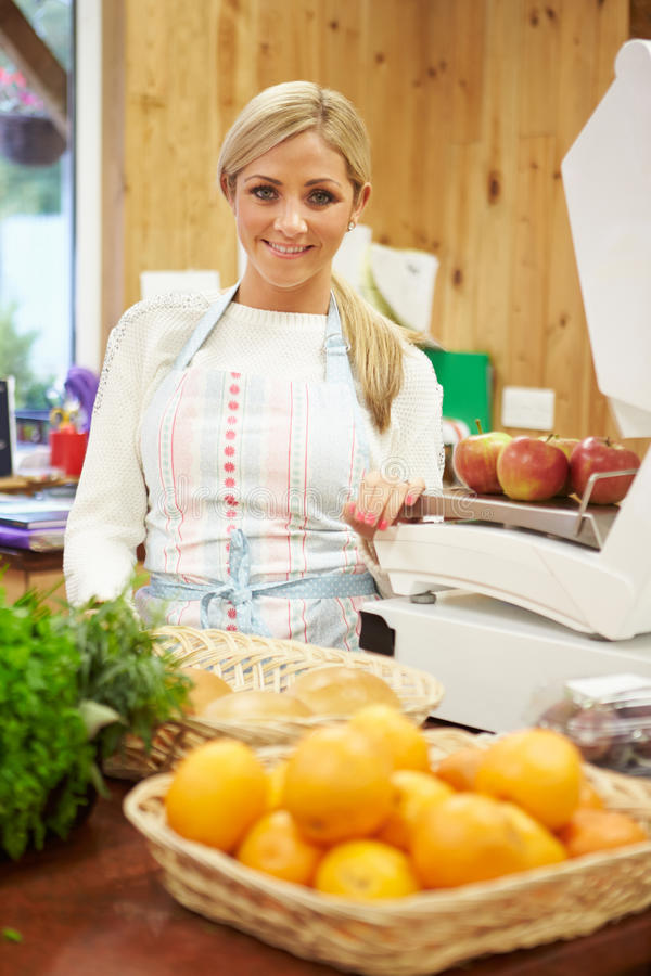 Female Sales Assistant At Checkout Of Farm Shop royalty free stock images