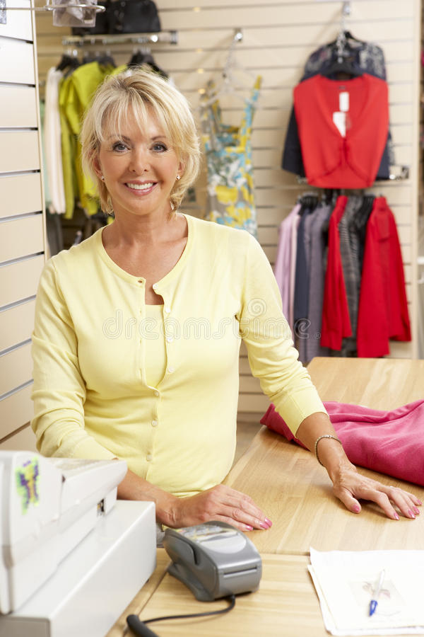 Female sales assistant in clothing store royalty free stock image