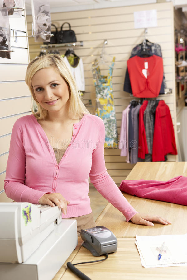 Female sales assistant in clothing store royalty free stock photography