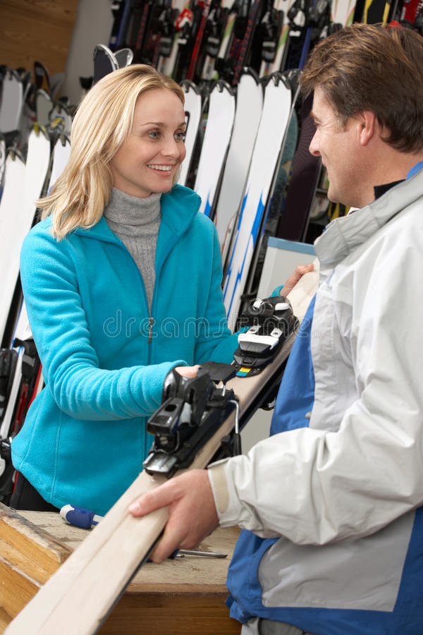 Female Sales Assistant Handing Skis To Customer royalty free stock image
