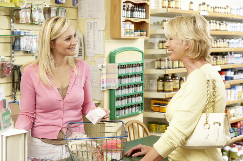 Female sales assistant in health food store stock image